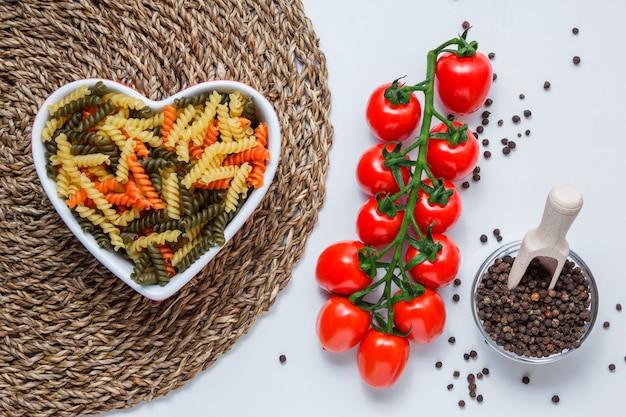 Pasta fusilli en un tazón con tomates, granos de pimienta en la vista superior primicia en blanco y mesa de mantel de mimbre
