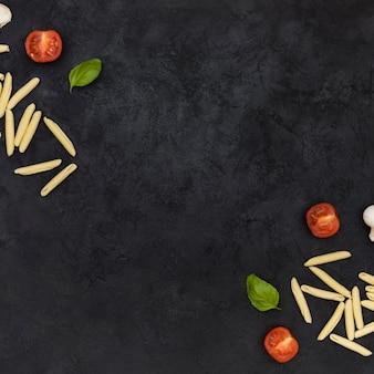 Pasta garganelli cruda con tomates a la mitad y albahaca en la esquina del fondo texturado negro