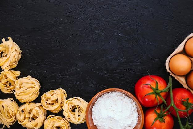 Pasta y harina cerca de tomates y huevos