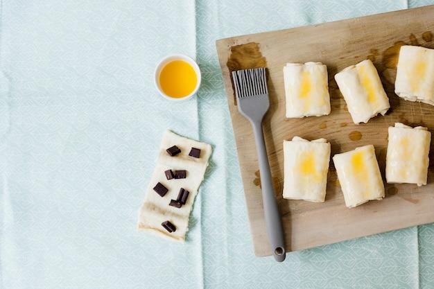 Pasta de hojaldre cruda doblada hecha en casa en una tabla de cortar de madera