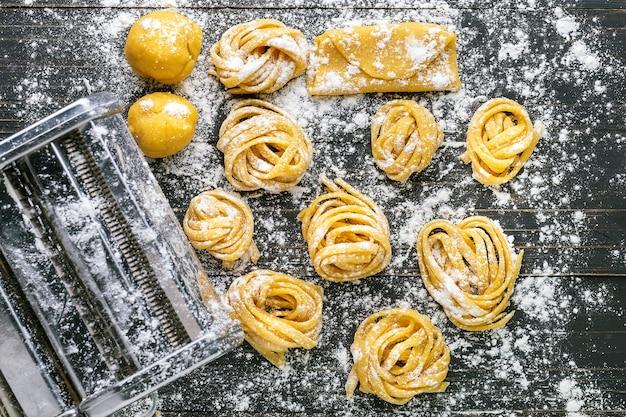 Pasta con ingredientes de pasta en la vista superior de la mesa de madera oscura