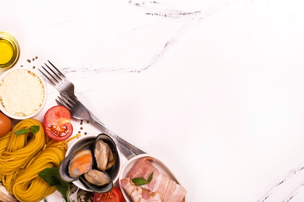 Pasta con ingredientes sobre mesa de mármol blanco.