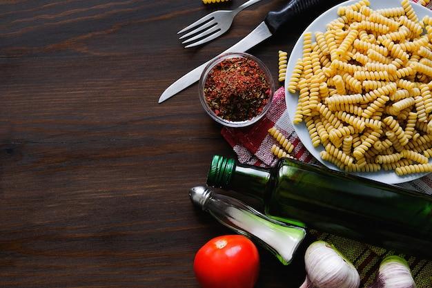 Pasta italiana, aceite de oliva, especias en una mesa de madera oscura.