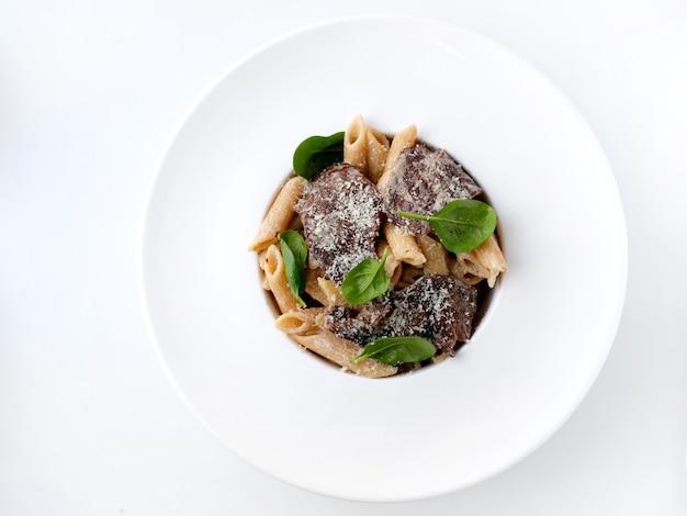 Pasta italiana con carne, pollo, rebanadas, queso, pesto y hojas verdes en la amplia placa blanca vista superior en fondo blanco.