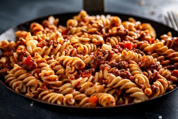 Pasta italiana clásica con carne picada y verduras cocidas y servidas en sartén. de cerca.