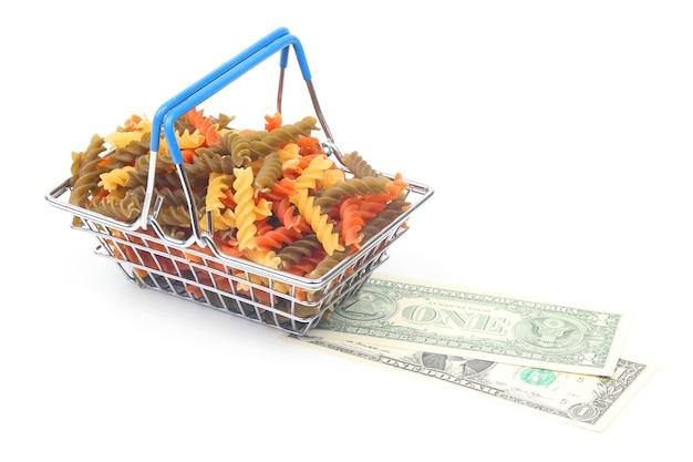 Pasta italiana de colores en una cesta de la compra del mercado con un billete de un dólar sobre un fondo blanco. productos de harina y alimentos en la cocina