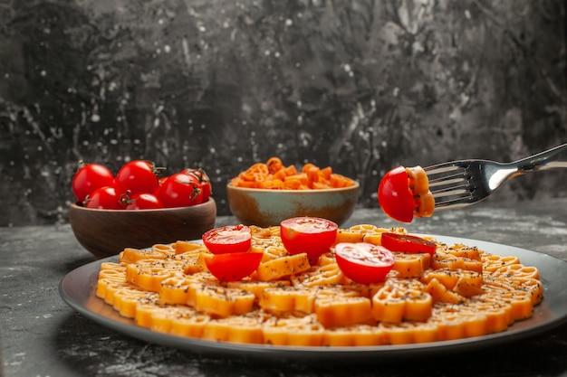 Pasta italiana de corazón vista frontal con tomates en plato redondo tomates en un tazón sobre fondo oscuro