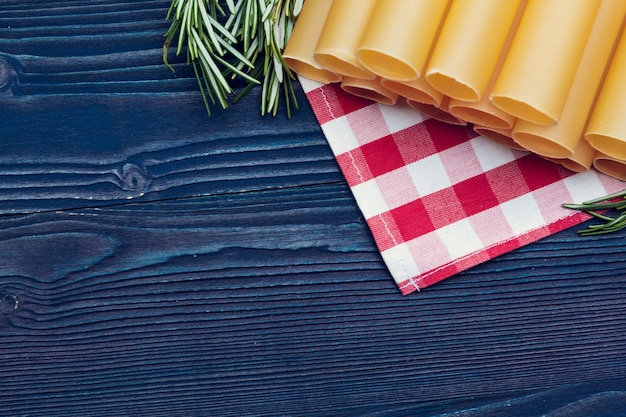 Pasta italiana cruda en la mesa de madera azul oscuro, vista superior de fondo