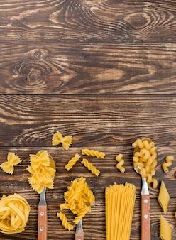 Pasta italiana en cucharas con espacio de copia