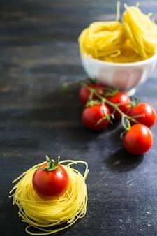 Pasta italiana e ingredientes sobre fondo de madera