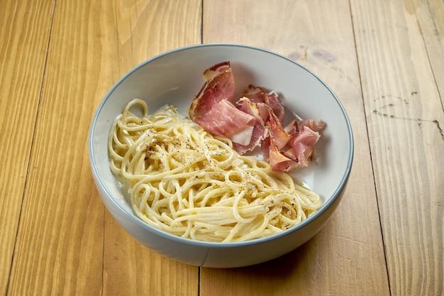 Pasta italiana (espagueti) con crema ahumada y tocino. pasta carbonara. cocina italiana