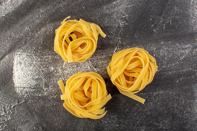 Pasta italiana en forma de vista frontal en forma de flor cruda y amarilla sobre gris