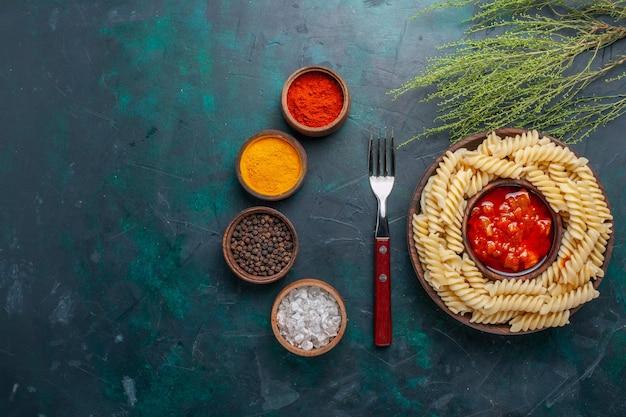 Pasta italiana en forma de vista superior con salsa de tomate y condimentos en el escritorio azul oscuro