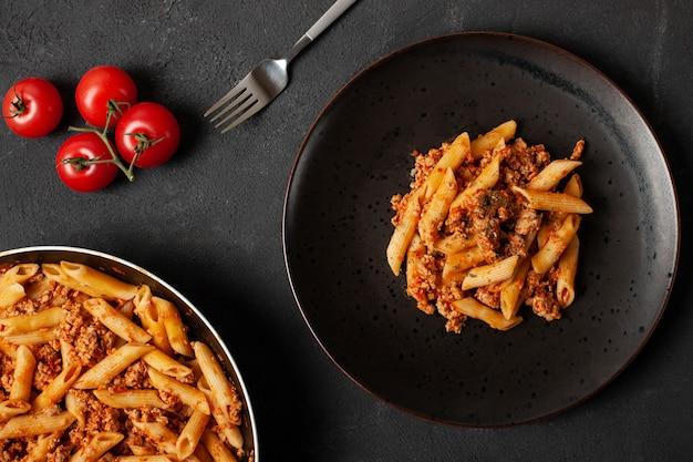 Pasta italiana fresca penne boloñesa con tomates cherry en plato oscuro
