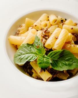 Pasta italiana penne con especias y albahaca dentro de un tazón blanco en fondo blanco.