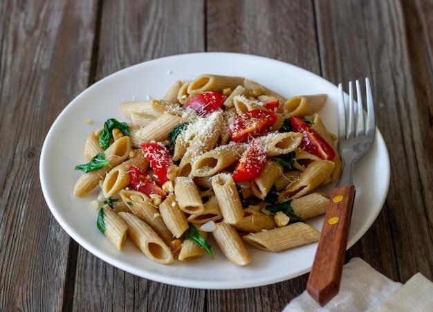 Pasta italiana penne con tomate, espinacas, queso parmesano, ajo y nueces. alimentación saludable. comida vegetariana.