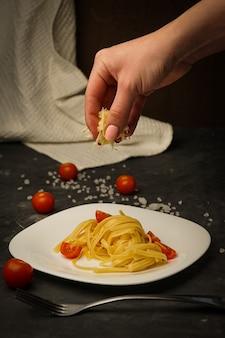 Pasta italiana en un plato en un oscuro con tomates cherry