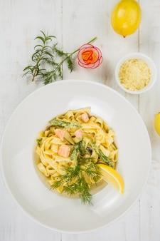 Pasta italiana con salmón y hierbas en mesa blanca
