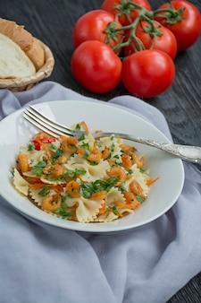 Pasta italiana en una salsa con camarones en un plato, vista superior. de madera oscura. .
