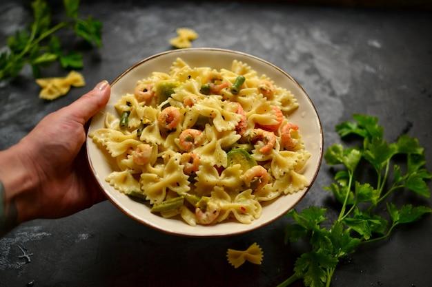 Pasta italiana en una salsa cremosa con camarones en un plato, vista desde arriba. camarones farfalle sobre una mesa oscura. las manos en el marco. la niña sostiene un plato hermoso con comida de pasta.