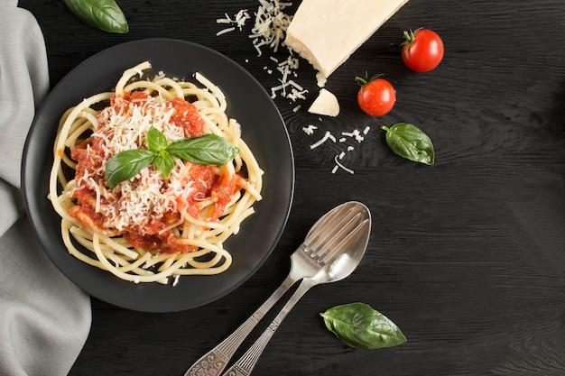 Pasta italiana con salsa de tomate y parmesano en la placa negra en la superficie de madera oscura. vista superior. copia espacio