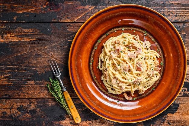 Pasta italiana spaghetti carbonara con tocino, queso parmesano duro y salsa de crema. oscuro