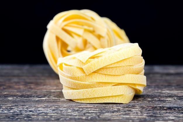 Una pasta larga retorcida hecha de harina de trigo, cerca de alimentos sólidos crudos