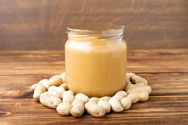 Pasta de maní cremosa en frasco de vidrio abierto, cuchara de mantequilla de maní, maní en la cáscara esparcida sobre la mesa de madera marrón