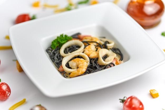 Pasta de marisco negro italiano casero con camarones, mejillones en fondo blanco.