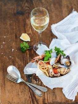 Pasta con mariscos. espaguetis con almejas y gambas en un tazón, copa de vino blanco