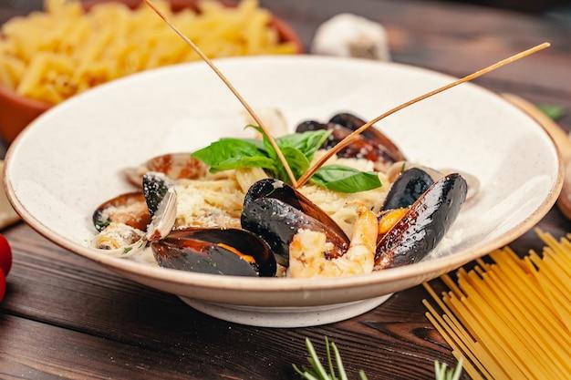 Pasta de mariscos con mejillones y albahaca en placa sobre mesa de madera