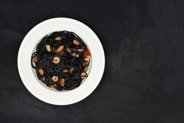 Pasta de mariscos negro en plato blanco sobre fondo negro con espacio de copia.