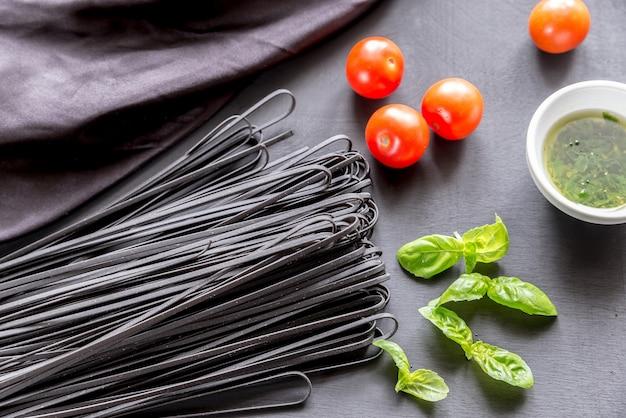 Pasta negra cruda con albahaca y tomates