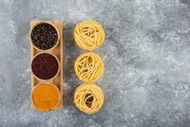 Pasta nido cruda con especias sobre una mesa gris.