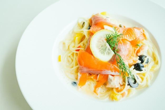 Pasta o salsa de espagueti con carne de salmón y limón encima.