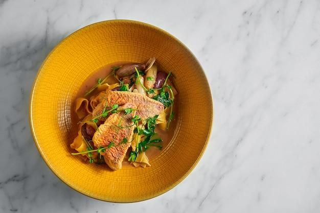 Pasta pappardelle con salmonete frito, barbule y microgrine en un plato amarillo brillante sobre blanco mármol