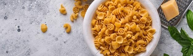 Pasta. pasta italiana. insalata di pasta y verduras para cocinar ingredientes, queso y albahaca sobre fondo de piedra vieja. ingredientes para cocinar comida italiana. vista superior con espacio de copia.