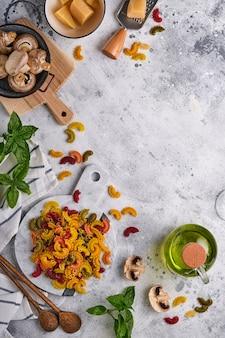 Pasta. pasta italiana. insalata di pasta y verduras ingredientes para cocinar, queso, champiñones y albahaca sobre fondo de piedra vieja. ingredientes para cocinar comida italiana. vista superior con espacio de copia.