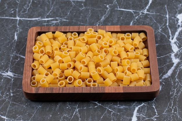 Pasta penne sin cocer en placa de madera sobre negro.
