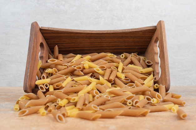 Pasta penne cruda en canasta de madera