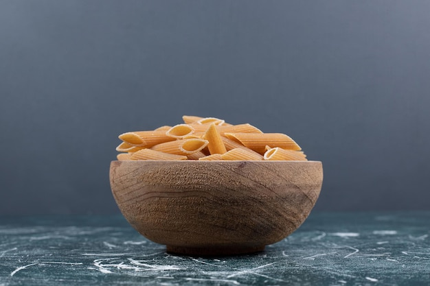Pasta penne cruda marrón en un tazón de madera.