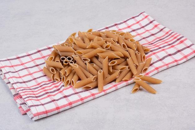 Pasta penne marrón cruda sobre mantel rayado.