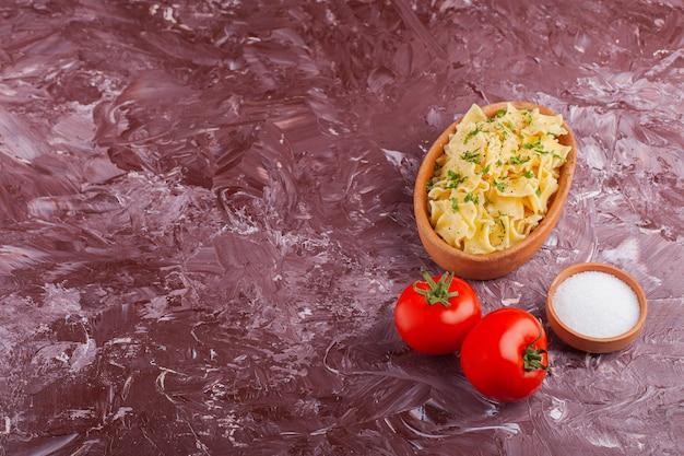 Pasta penne con mayonesa y tomates rojos frescos sobre una mesa de luz.