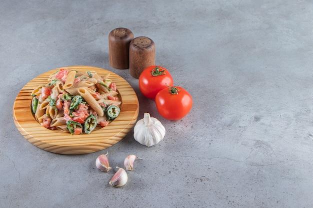 Pasta penne sabrosa con verduras frescas picadas en placa de madera.