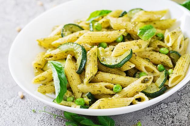 Pasta penne con salsa de pesto, calabacín, guisantes y albahaca. comida italiana.