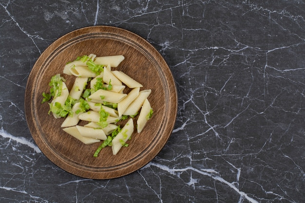 Pasta penne con salsa de verduras sobre tabla de madera.