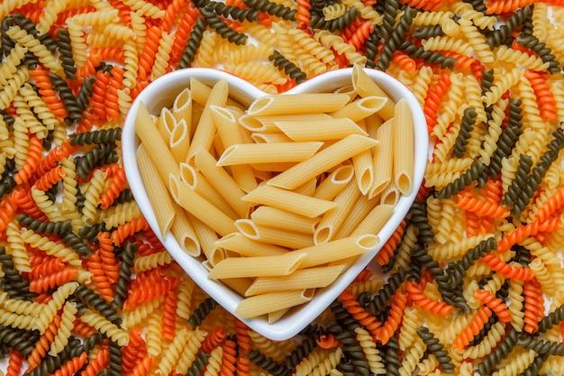 Pasta penne seca en un plato plano en forma de corazón sobre una mesa fusilli de colores