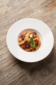 Pasta penne con tomate, aceitunas y albahaca. penne de pasta arrabiata en tazón de fuente blanco