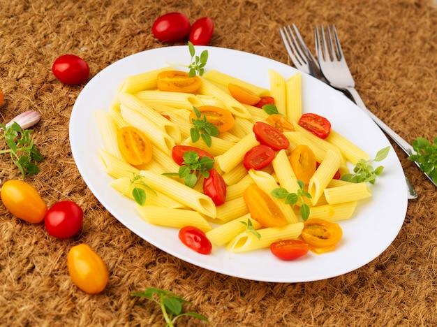 Pasta penne con tomates amarillos y rojos decorados con albahaca sobre sisal, comida dietética baja en calorías