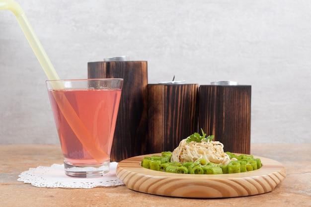 Pasta penne verde y fideos en placa de madera con vaso de jugo